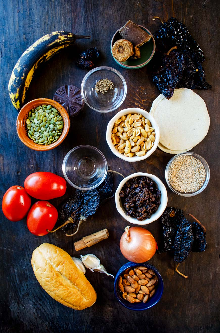 Ingredients for mole poblano recipe displayed on a dark wooden board