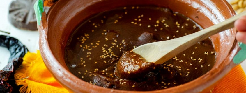 Spoon scooping mole poblano out of clay pot