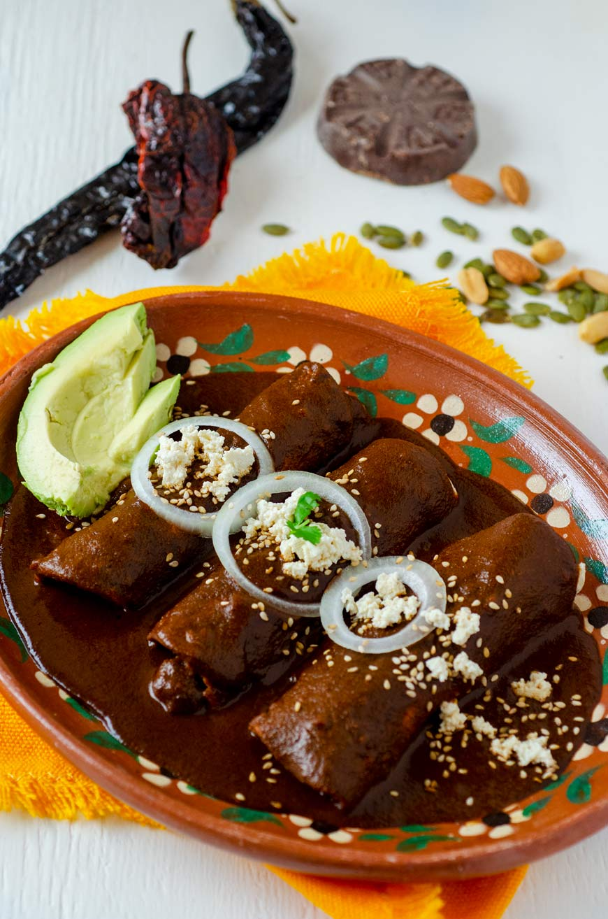 Enmoladas in a clay plate surrounded by mole ingredients