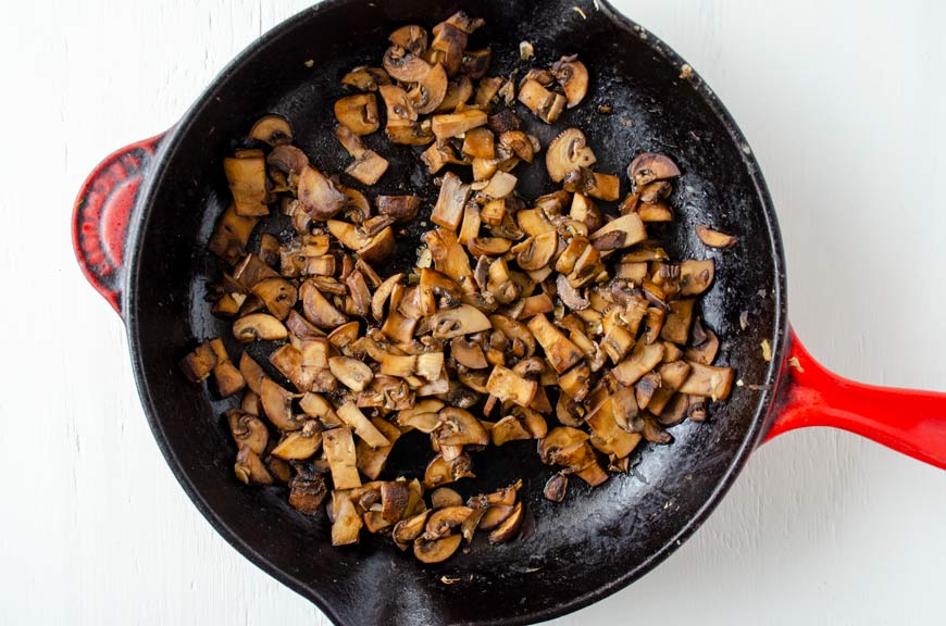 Cast iron pan with sauteed mushrooms for vegan potato enchiladas