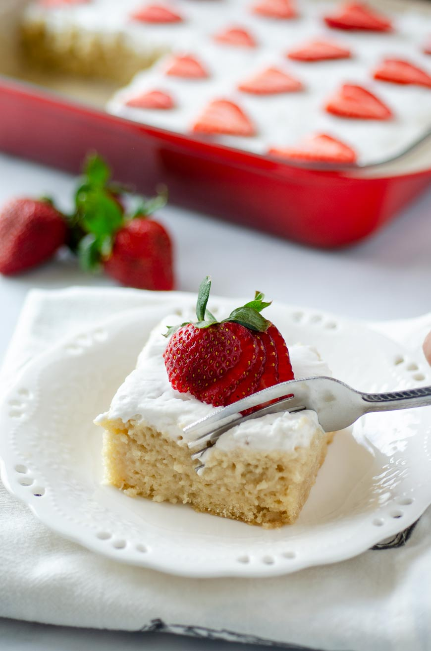 Tres leches cake on a white plate topped with a sliced strawberry