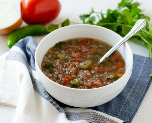 Mexican vegan lentil soup in a white bowl surrounded by tomato, cilantro and onion