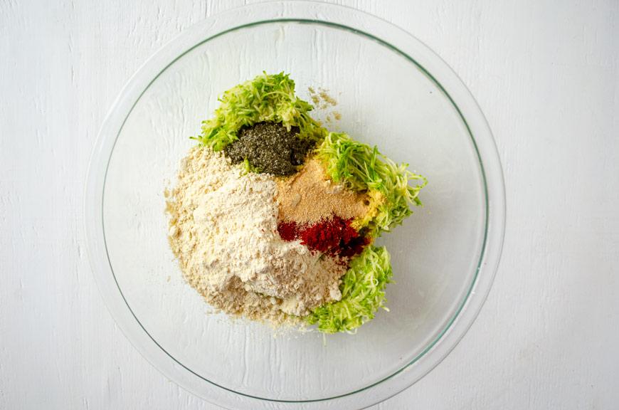 Glass bowl with chickpea flour, zucchini, spices, and nori powder for vegan tortitas de camaron