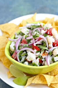 Cauliflower ceviche with red onion, tomato, cilantro in a green bowl surrounded by chips