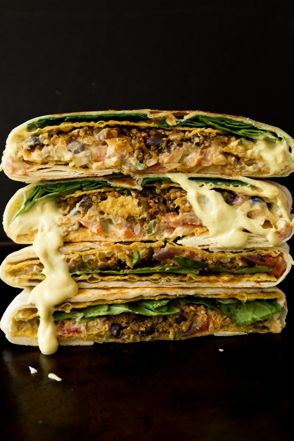vegan crunch wrap stacked on top of each other with sauce dripping down the sides