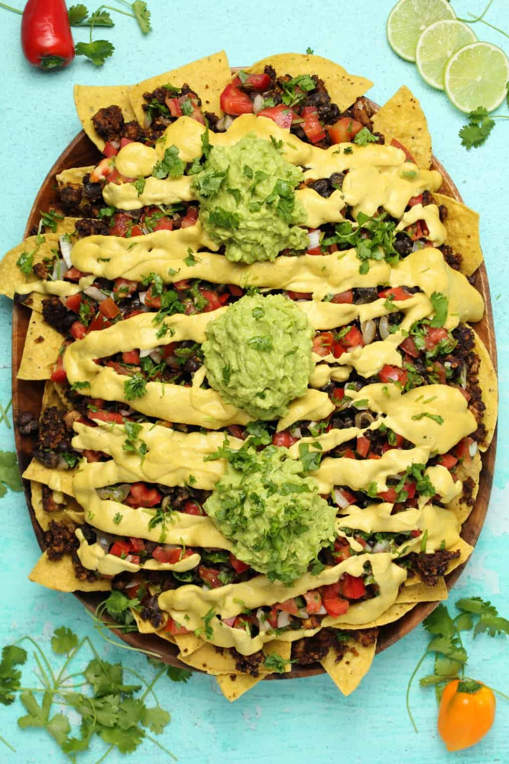 vegan nachos in a large oval platter on a teal background
