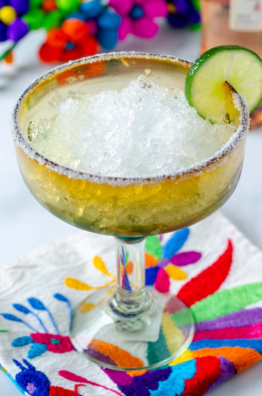 salt rimmed margarita glass filled with crushed ice on top of a colorful napkink