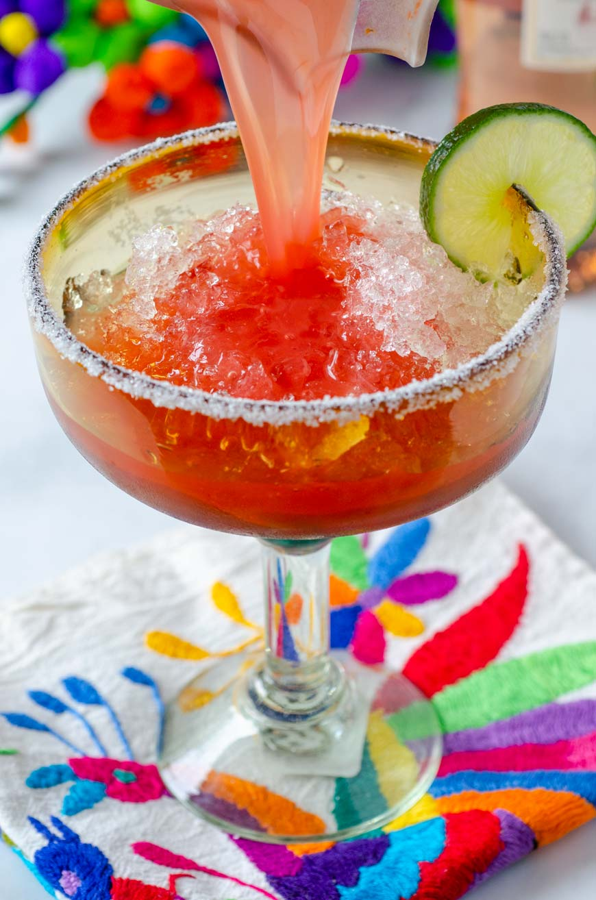 strawberry frose margarita poured over margarita glass with ice