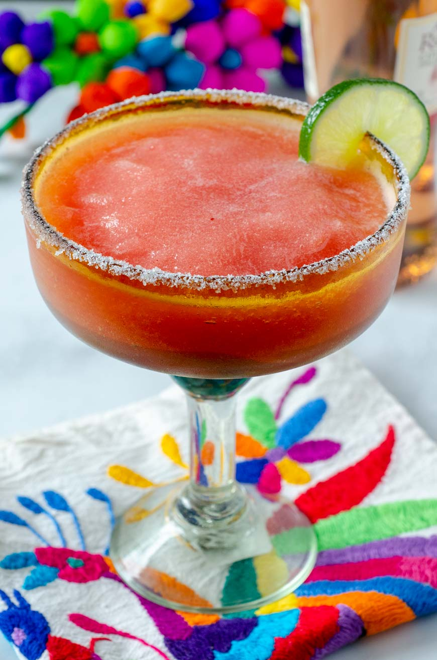 Strawberry frose margarita in a salt rimmed margarita glass decorated with a lime slice