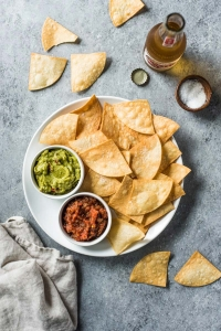 homemade chips on a white plate with avocado and salsa