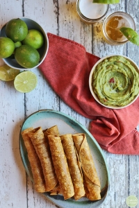 flautas or taquitos in an oval green plate surrounded by a red towel limes and avocado