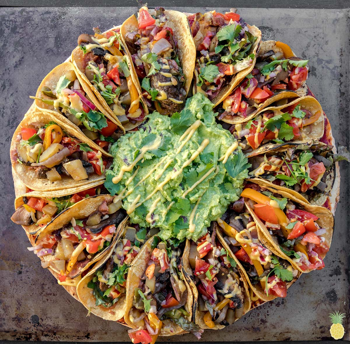 a pizza topped with guacamole in the center and surrounded by veggie tacos