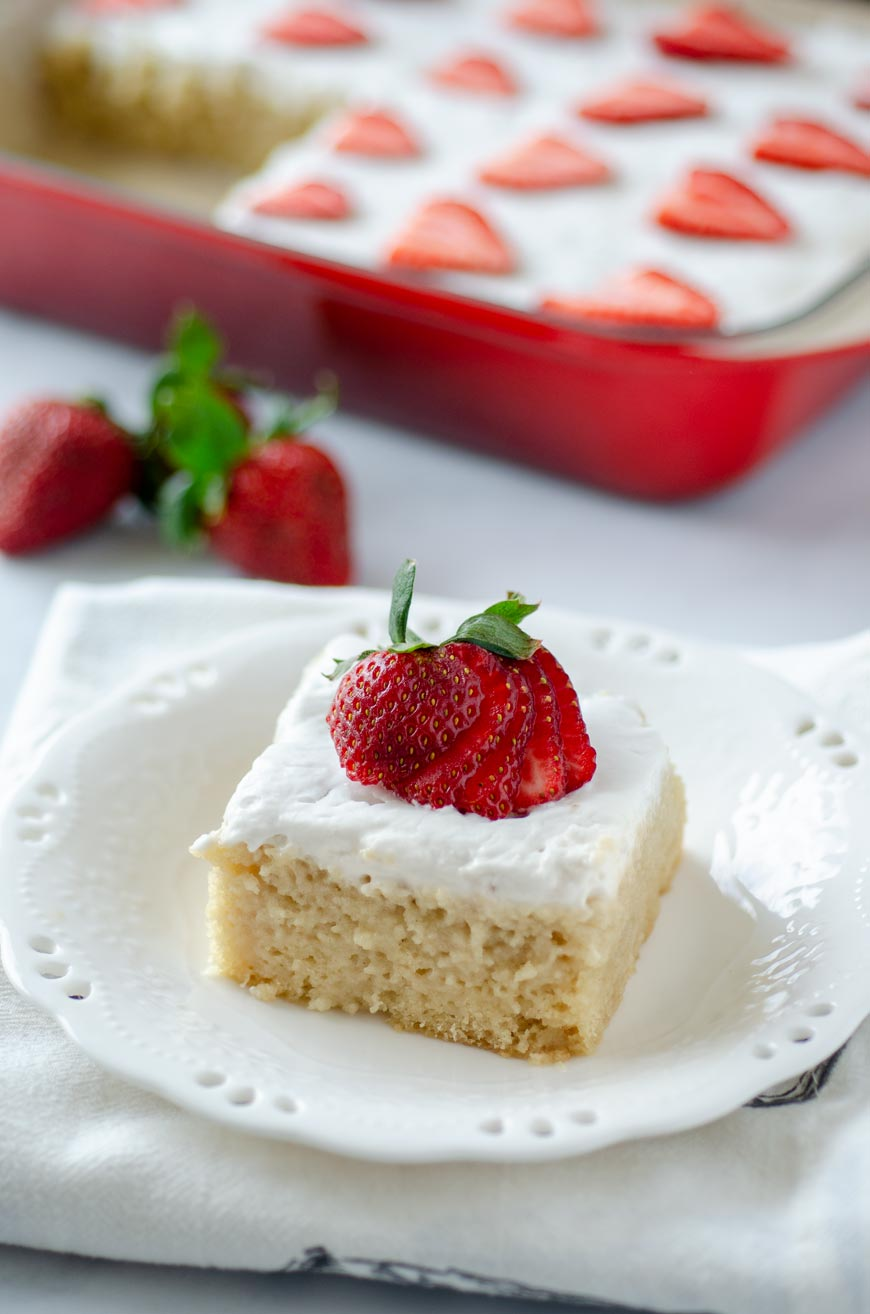 a slices of vegan tres leches cake topped with a strawberry for cinco de mayo party food ideas