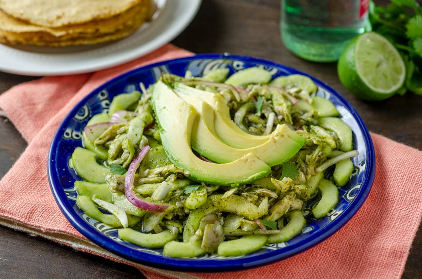 Vegan aguachile verde on a blue talavera plate on top of a melon colored cloth napkin.