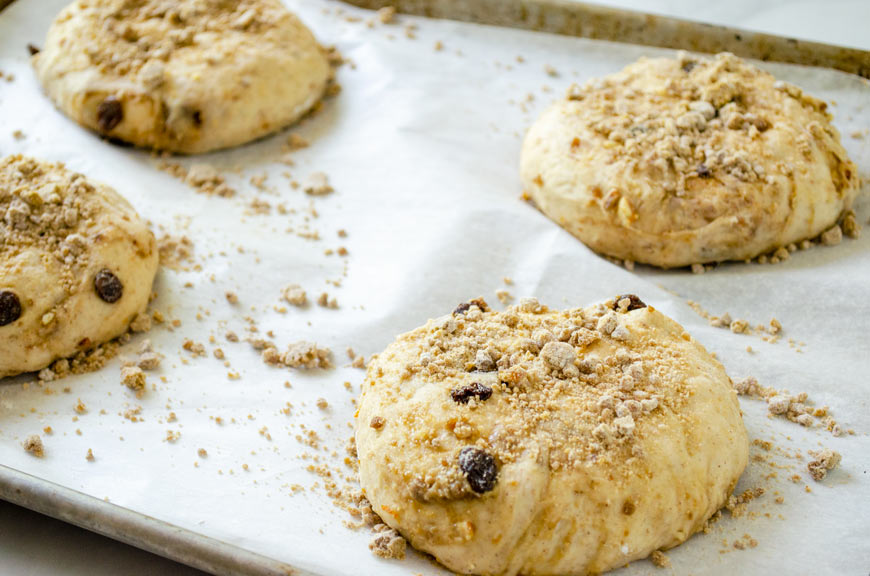 four balls of dough on a parchment lined sheet tray