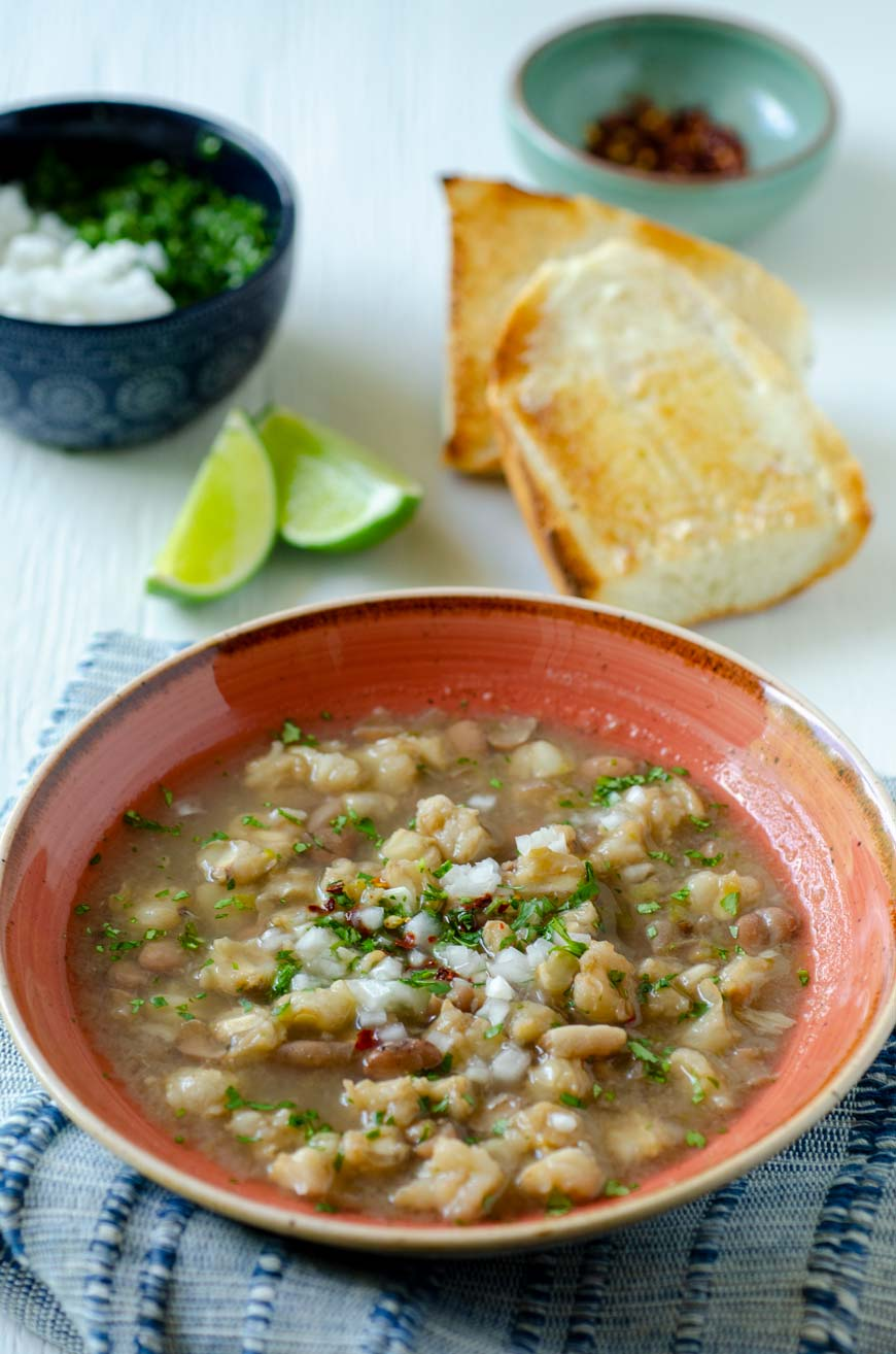 Gallina pinta soup in a melon colored bowl with toast on the side