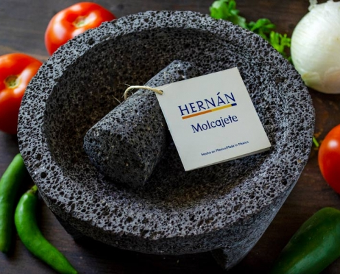 Hernan molcajete surrounded by tomato, onion, and peppers