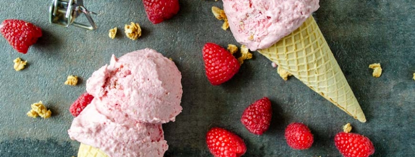 Two raspberry ice cream cones on top of a black background surrounded by oatmeal crumble and raspberries