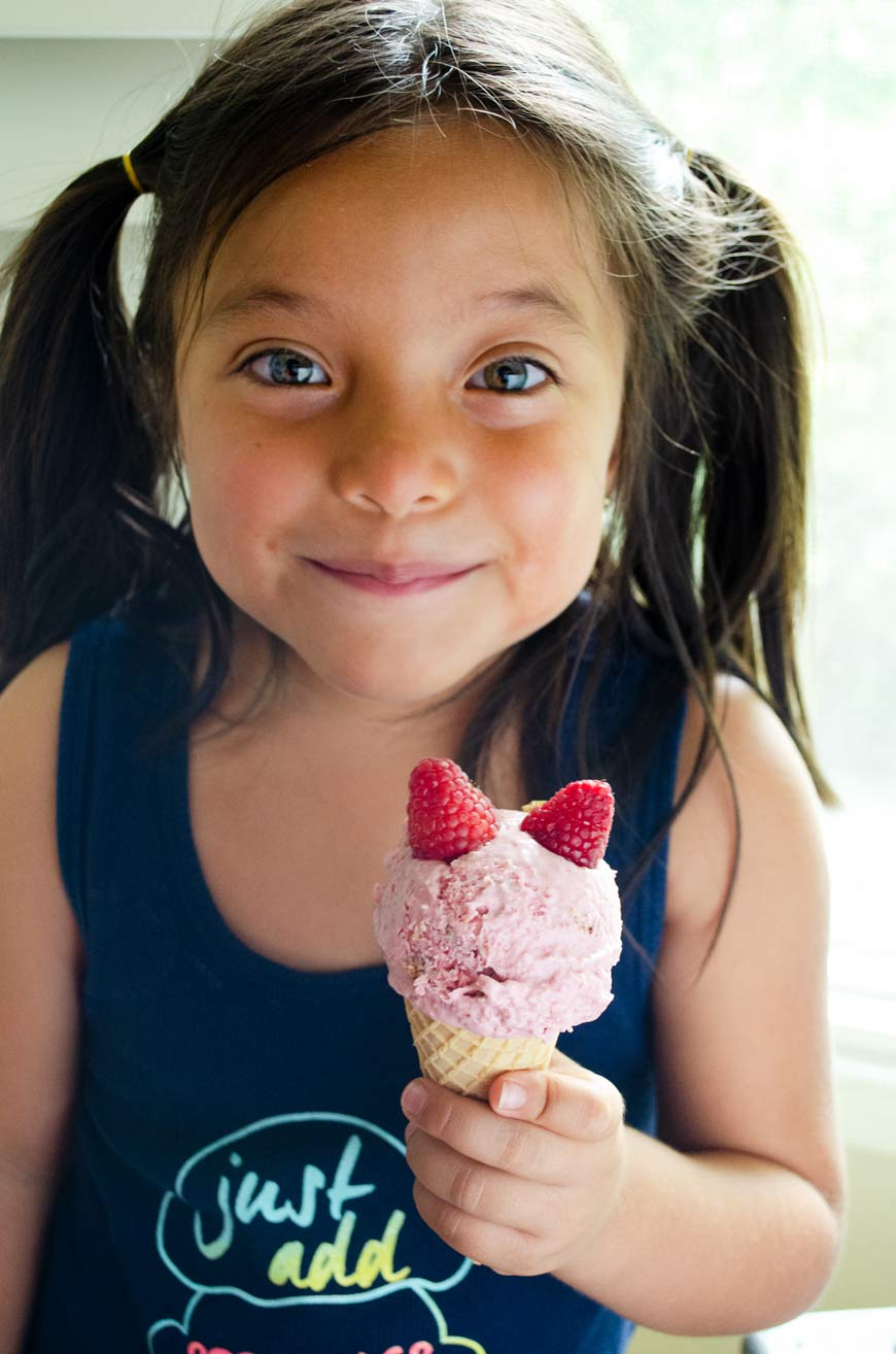 Little girl with pigtails, blue eyes, and olive skin holding a sugar cone with raspberry ice cream topped with two raspberries