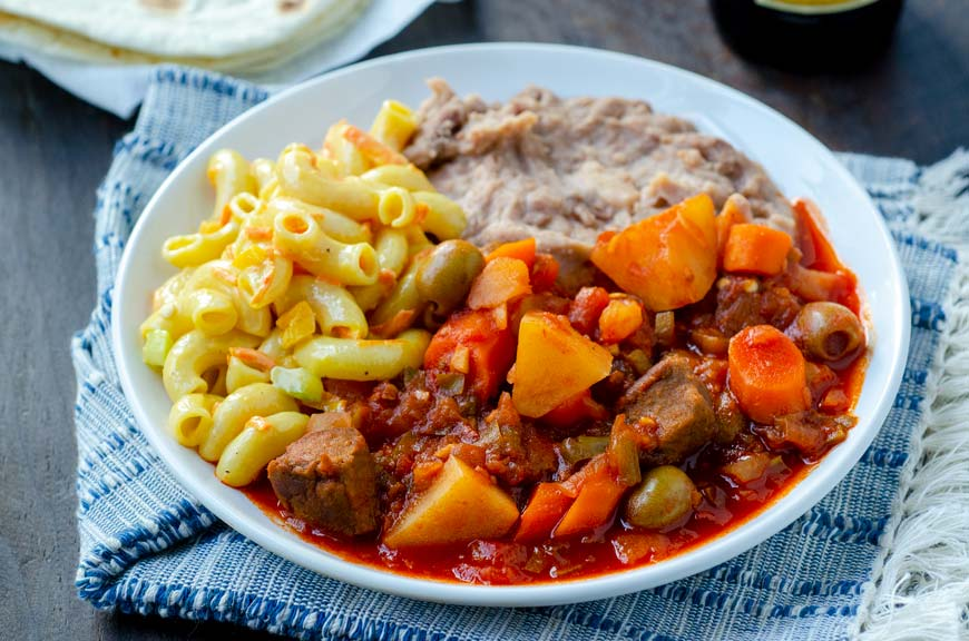 Vegan barbacoa sinaloense on a white plate with macaroni salad and refried beans