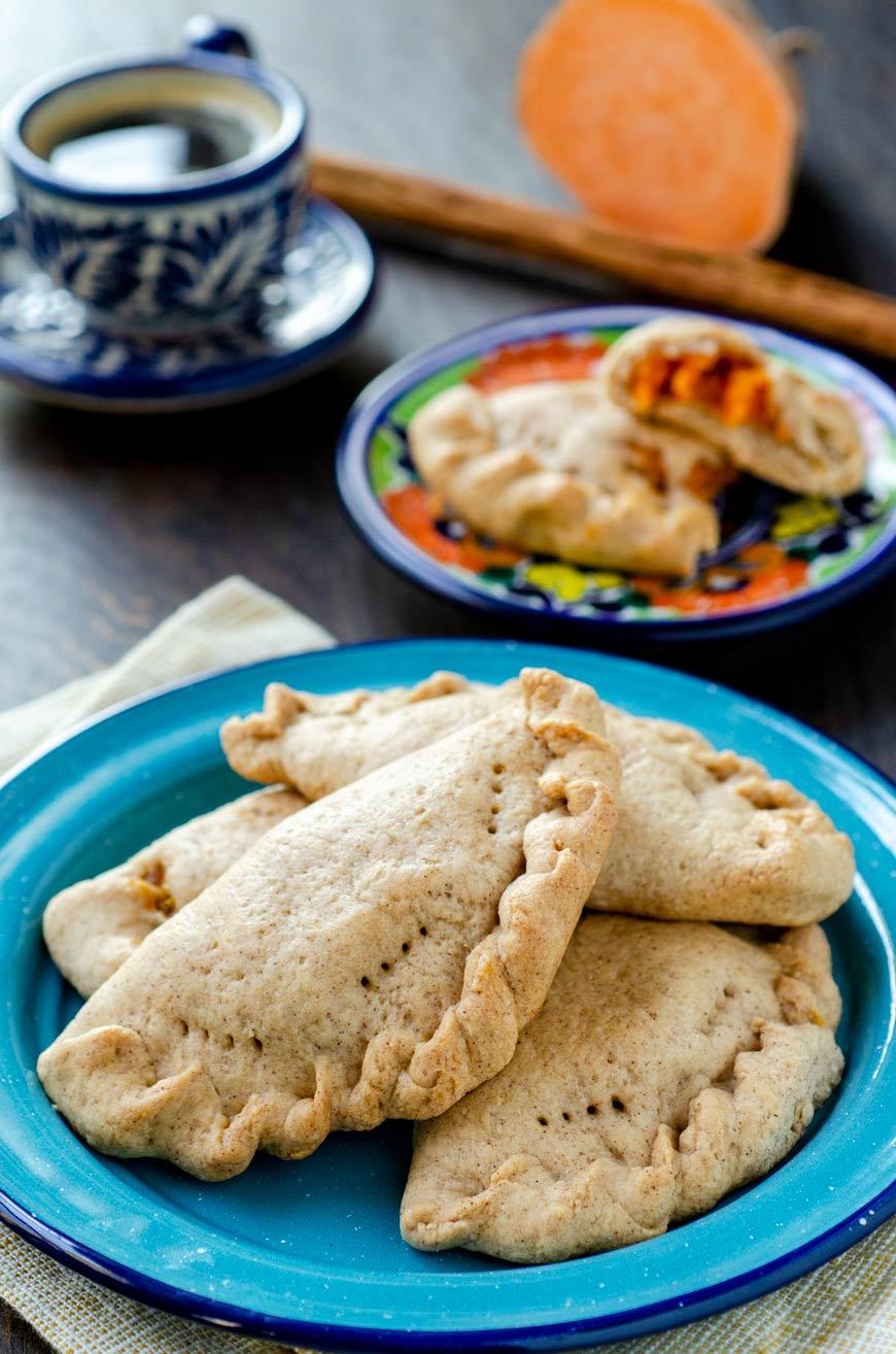 Empanadas de camote on a blue plate, cup of coffee and cinnamon stick