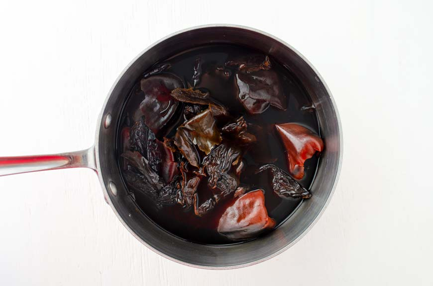 Dried chiles soaking in water in a stainless steal pot.