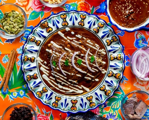 Mole negro enmoladas on a talavera plate and a bright orange tablecloth with flowers behind it.