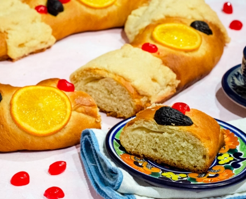 Vegan rosca de reyes on a pink back ground with a piece set in front of it on a plate.