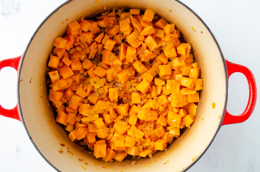 Diced sweet potatoes, onion, and garlic in a large dutch oven