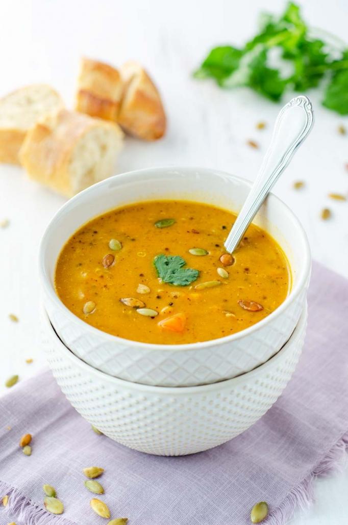 A spoon dipping into a bowl of smoky sweet potato soup.