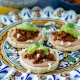 a close up 3 vegan sopes filled with beans, walnut meat, avocado salsa on a colorful talavera plate and yellow napkin underneath