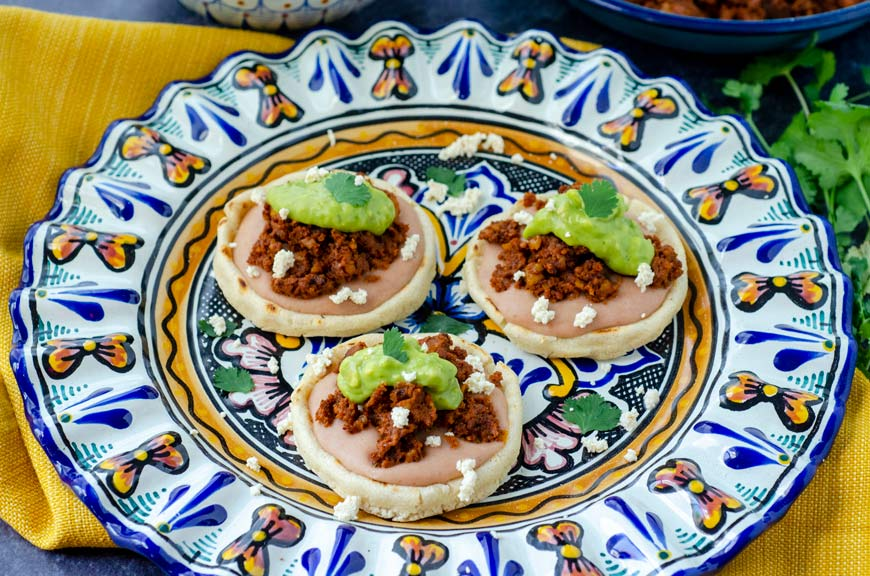3 vegan sopes filled with beans, walnut meat, avocado salsa on a colorful talavera plate and yellow napkin underneath