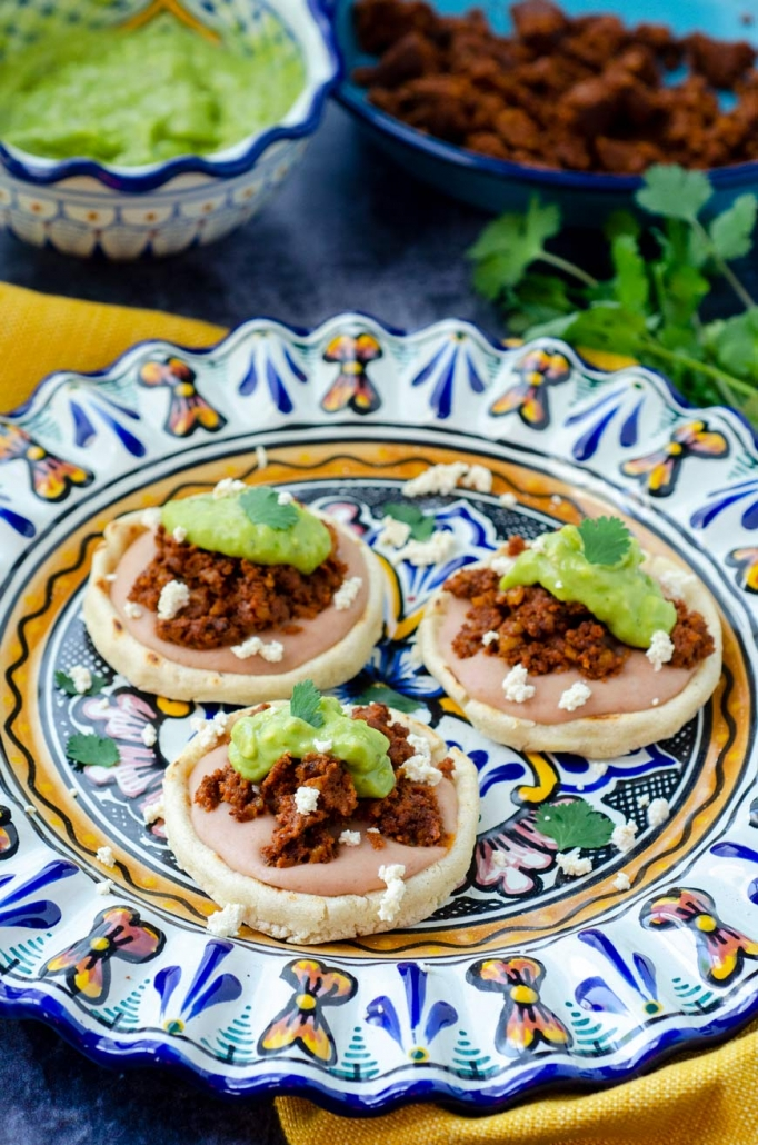3 sopes filled with beans, walnut meat, avocado salsa on a colorful talavera plate