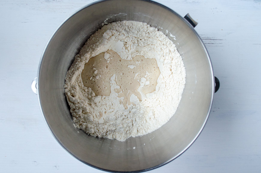 Flour, sugar, salt, and a yeast starter in a stainless steel metal bowl