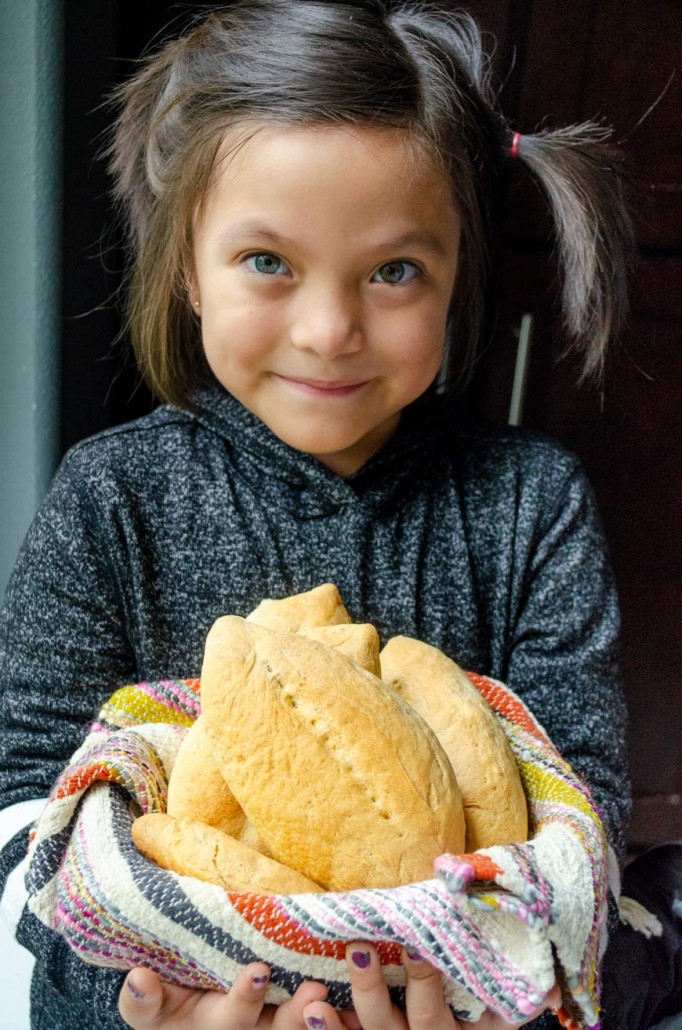 a little girl with pigtails wearing a black-gray sweater holding the basket of bolillos