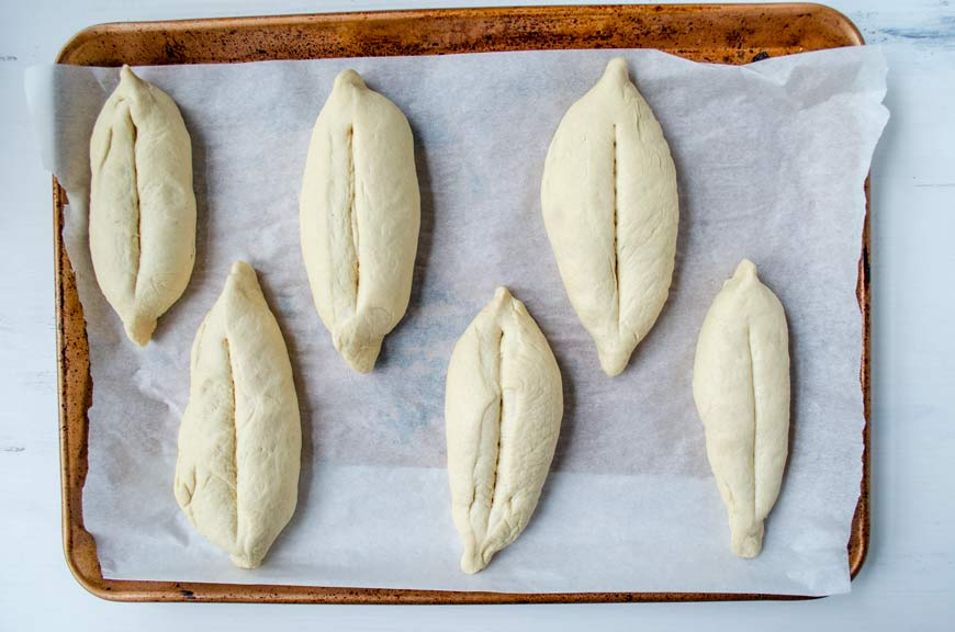 dough shaped into football shapes and placed on a parchment lined sheet tray
