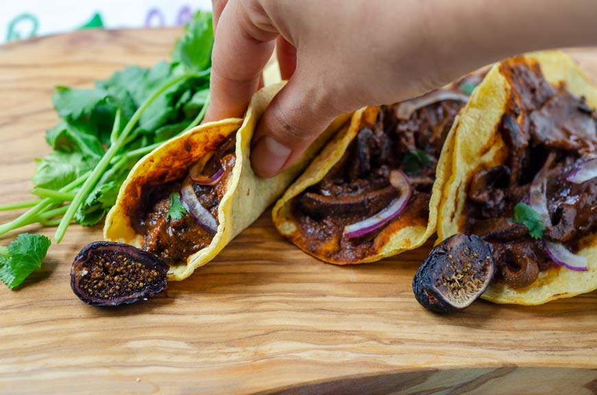close up of a hand taking a fig mole mushroom tacos on a wooden board with sliced figs and cilantro in the background