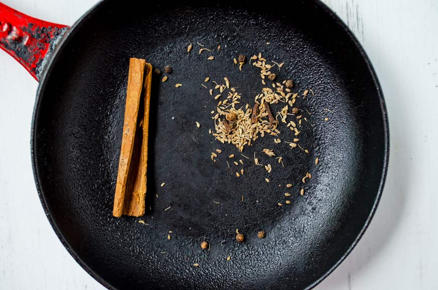 anise seeds, clove, and cinnamon toasting on a cast iron pan