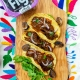 fig mole mushroom tacos on wooden board with an embroidered Otomi placemat and orchard choice fig pack