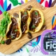 fig mole mushroom tacos on wooden board laid out at an angle with an embroidered Otomi placemat and orchard choice fig pack