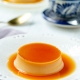 vegan flan on a small white laced plate with a coffee and another flan in the background