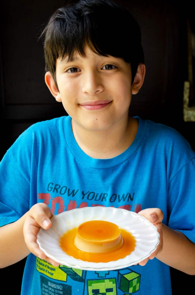 10 yr old boy wearing a blue shirt holding a plate with flan