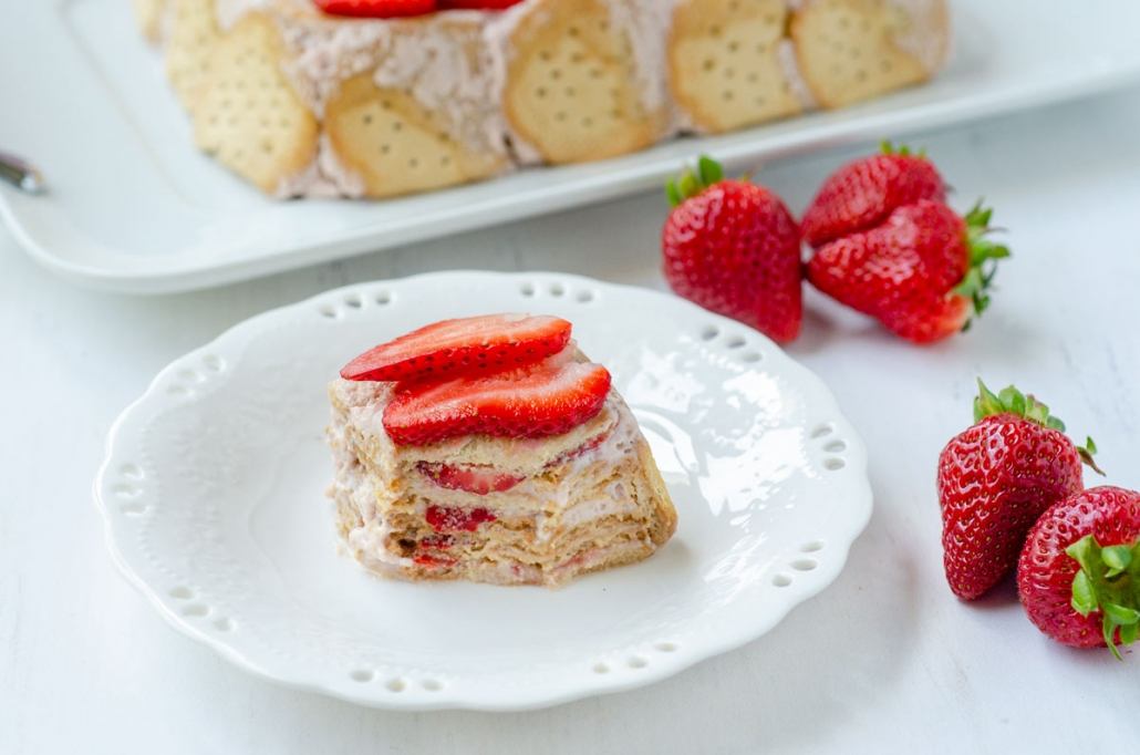 a wide shot of a spoonful taken out of a slice of carlota de limon showing the different layers and topped with sliced strawberries on top and surrounded by strawberries
