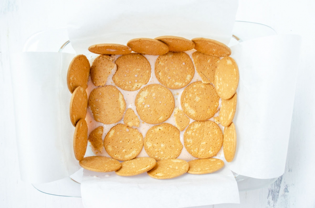 parchment paper lined glass baking dish lined with rows of Maria cookies
