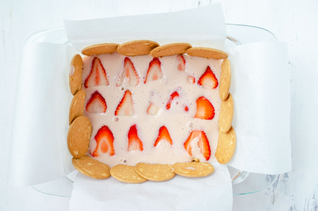 Parchment paper lined glass baking dish lined with Maria cookies, strawberry cream, and fresh strawberries.