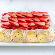 Vegan carlota de fresa, strawberry iced box cake topped with sliced strawberries, on a white serving tray with silver colored handles