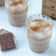 two glasses of horchata de chocolate, two cinnamon sticks and two chocolate squares beside it