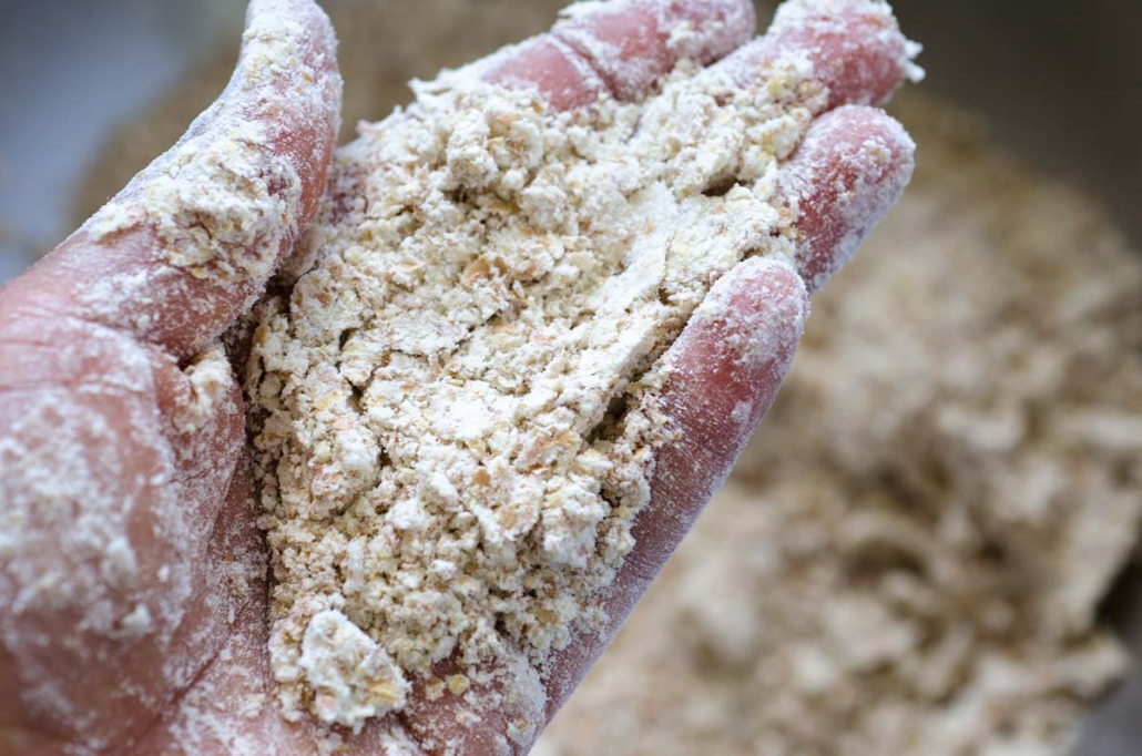 a hand up close showing the texture of the flour mixture