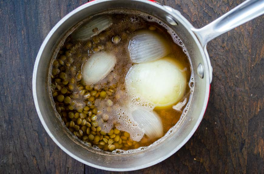 stainless steel pot full of lentils, onions, and broth on a wood background