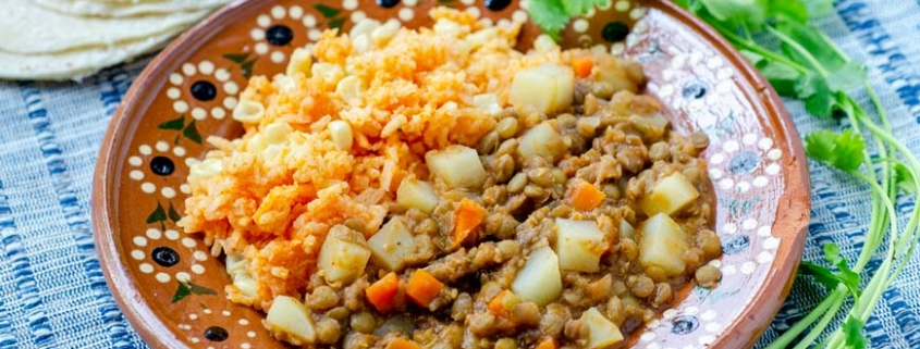 side angle of vegan picadillo and mexican rice in a clay plate on top of a striped blue placemat